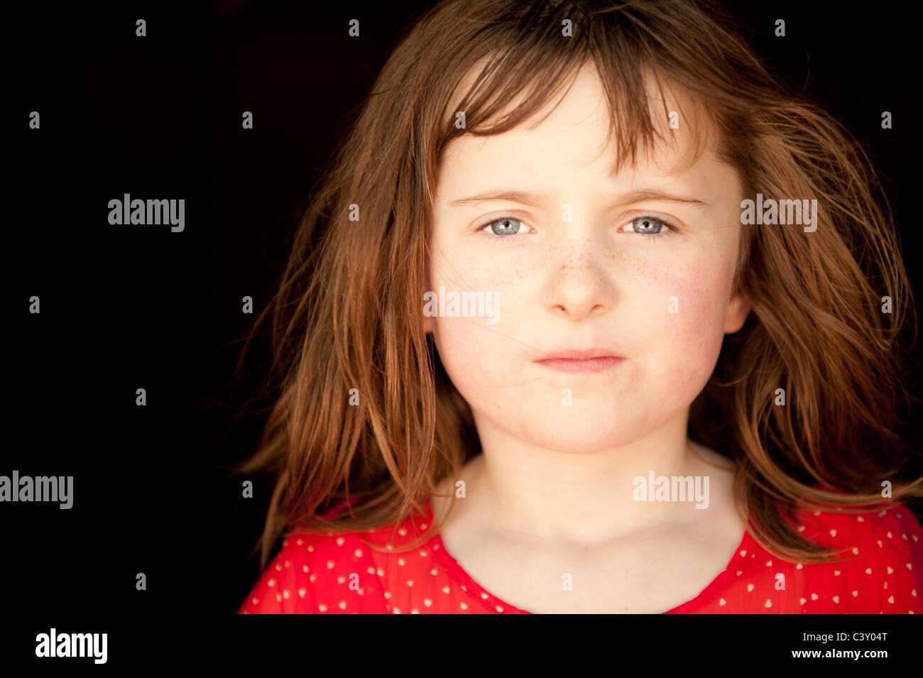 Bambina guardando la fotocamera con grave espressione facciale Immagini Stock
