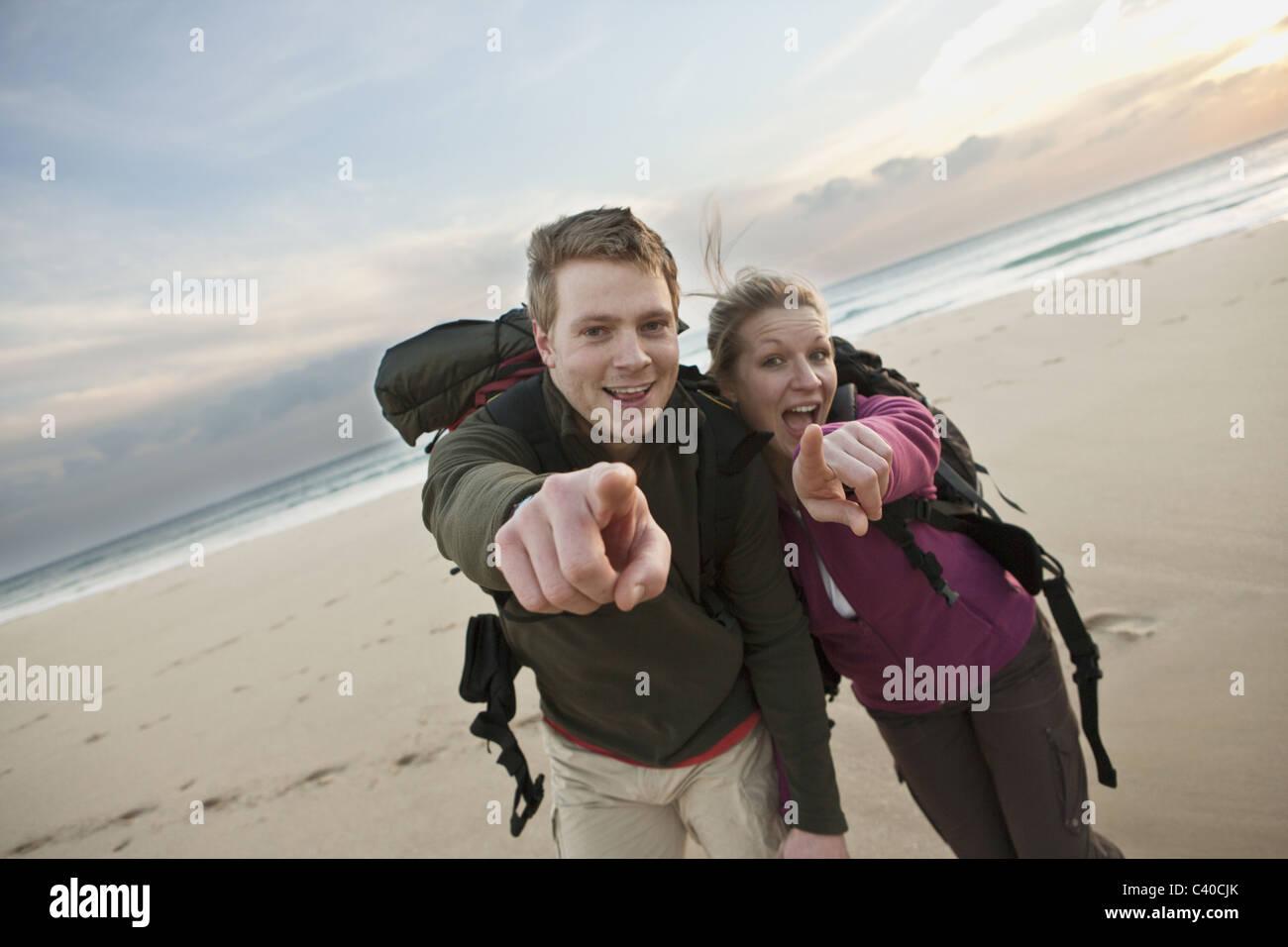 Backpacking giovane puntando alla fotocamera Immagini Stock