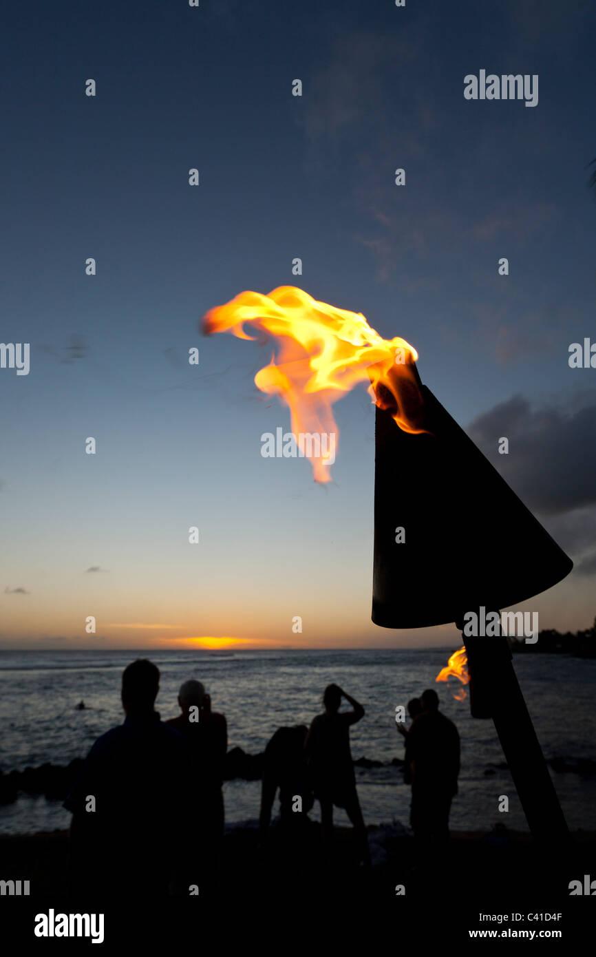 Visualizzazione del tramonto con torcia tiki. I visitatori di spiaggie del sud di Kauai si riuniscono ogni sera Immagini Stock