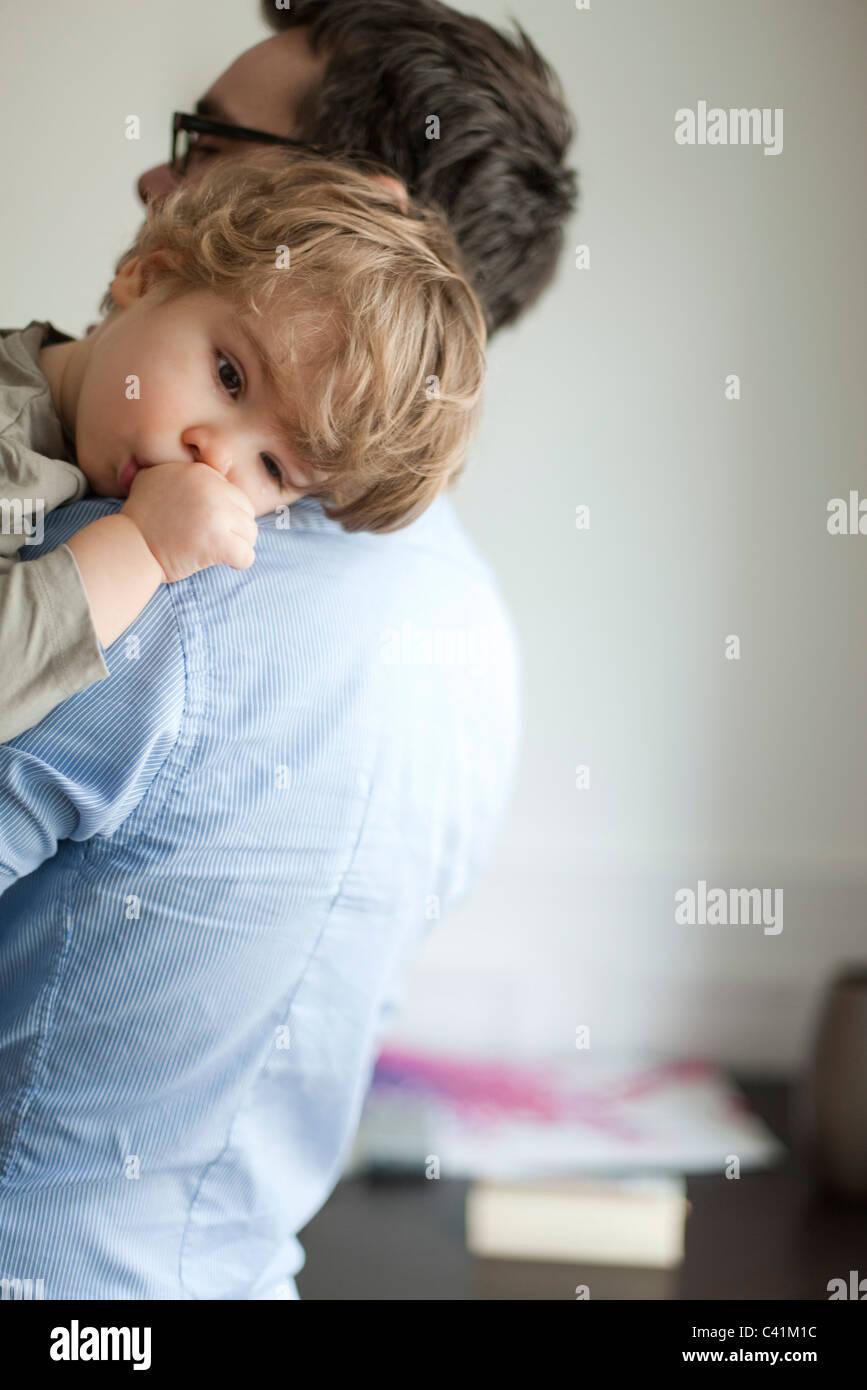 Il Toddler boy in appoggio sulla testa del padre shoudler Immagini Stock