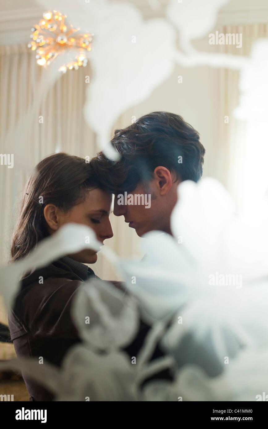 Giovane abbracciando, visto attraverso la finestra Immagini Stock