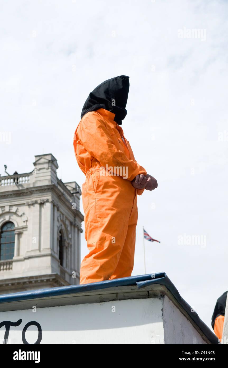 Un manifestante incappucciati vestita come una baia di Guantanamo prigioniero a Piazza del Parlamento, Londra, Inghilterra Immagini Stock
