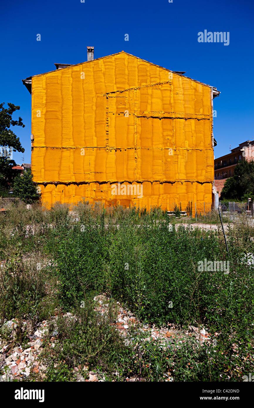 Fine della casa accanto alla demolita lotto con la parete protetta con materiale spruzzato per chiuderlo a tenuta Immagini Stock