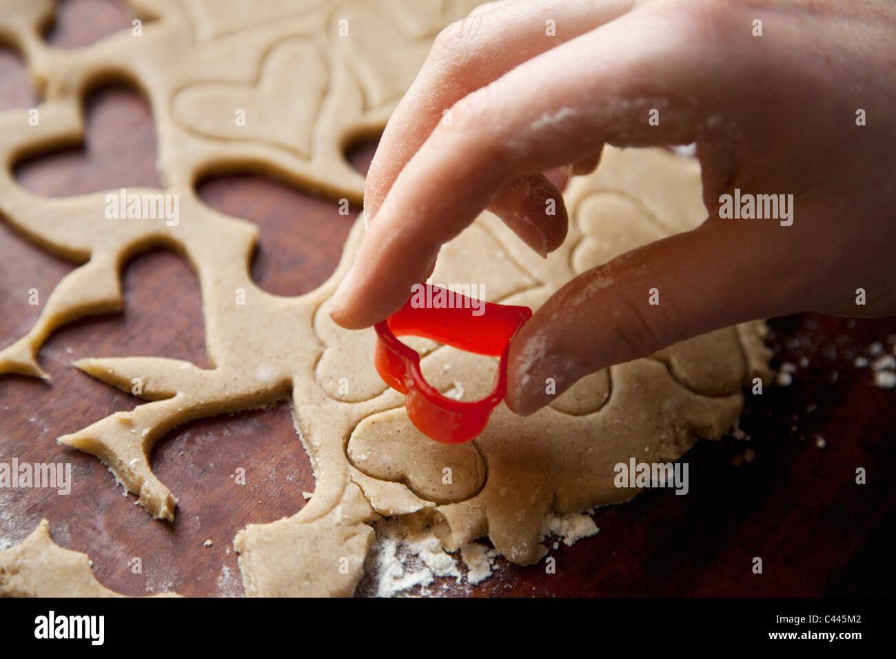 Dettaglio di una mano utilizzando una forma di cuore cookie cutter Foto Stock