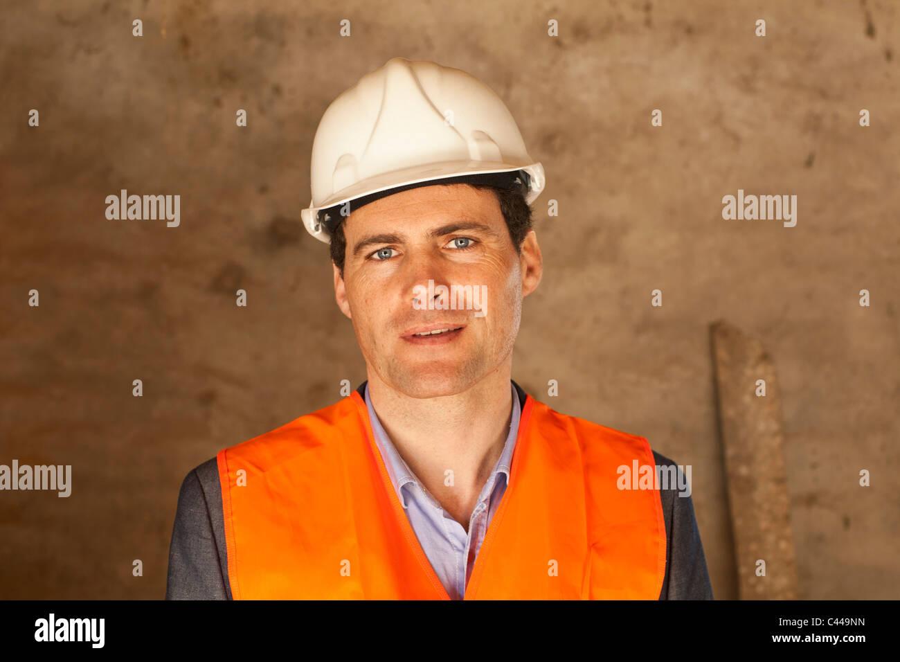 Un ben vestito che indossa un casco e giubbotto in corrispondenza di un sito di costruzione Immagini Stock