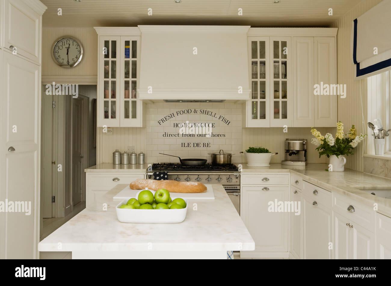 Con ripiano in marmo isola in cucina con le unità bianche e
