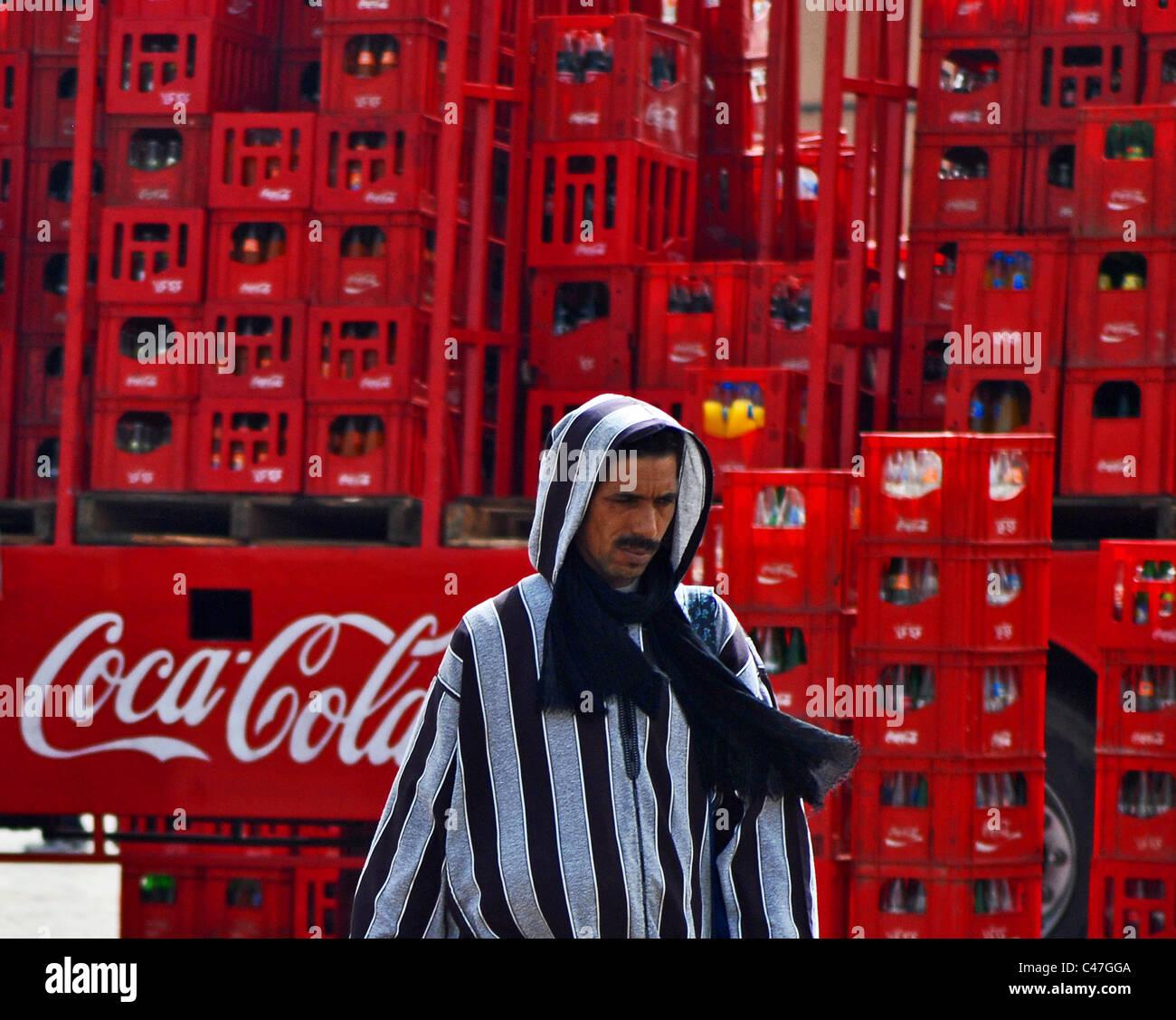 La globalizzazione. Coca Cola carrello e uomo arabo in abito tradizionale. Marrakech, Marocco Immagini Stock