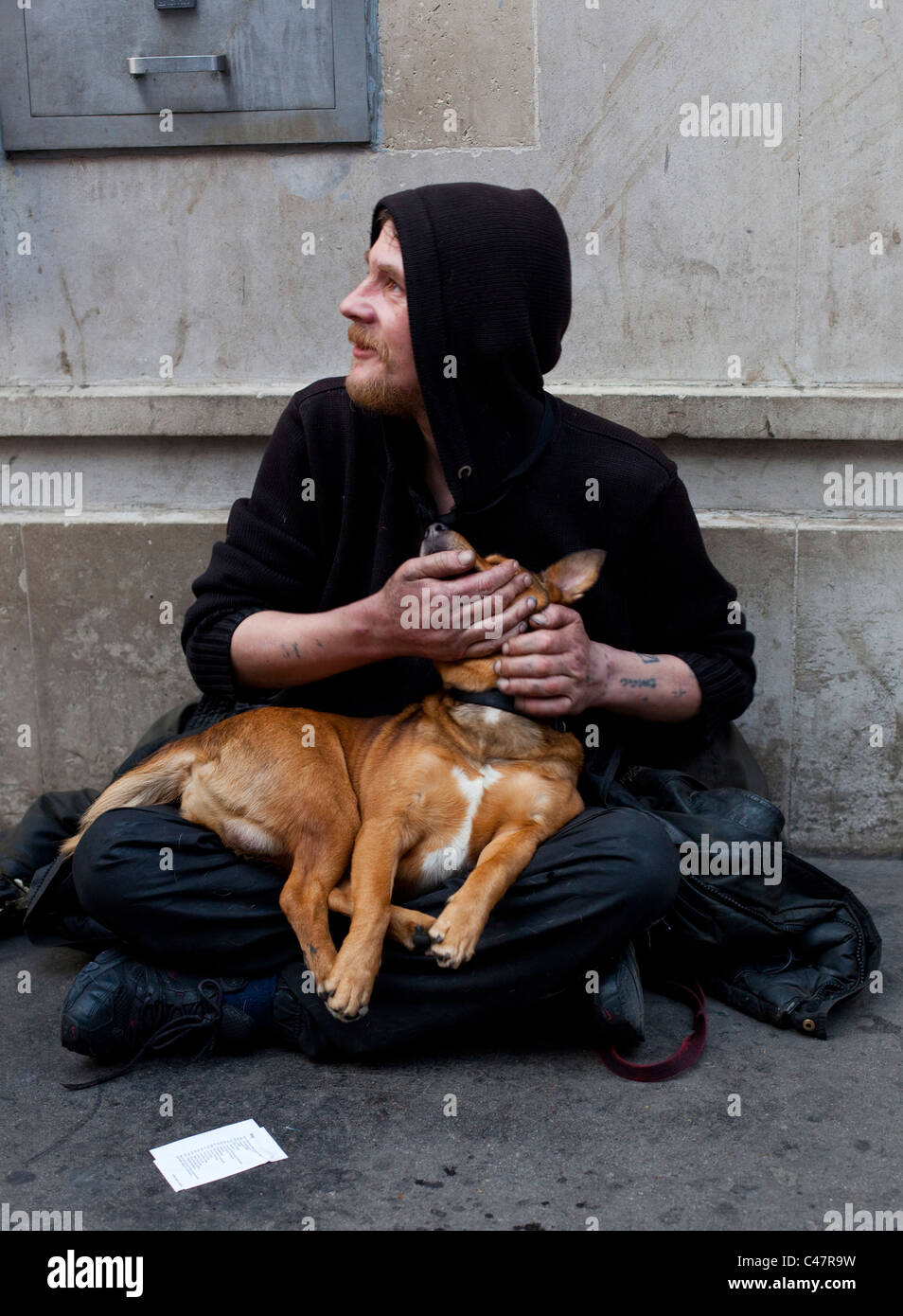 Un uomo senza tetto per l'accattonaggio denaro sul marciapiede e tenendo la sua pet fare, Londra, Inghilterra, Immagini Stock