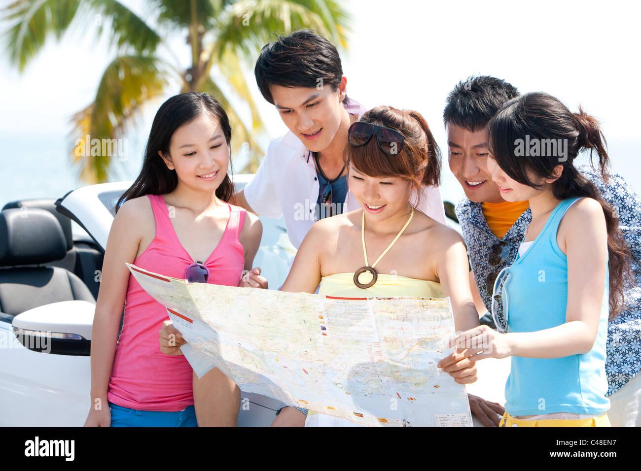 Gli amici in cerca di una mappa Immagini Stock