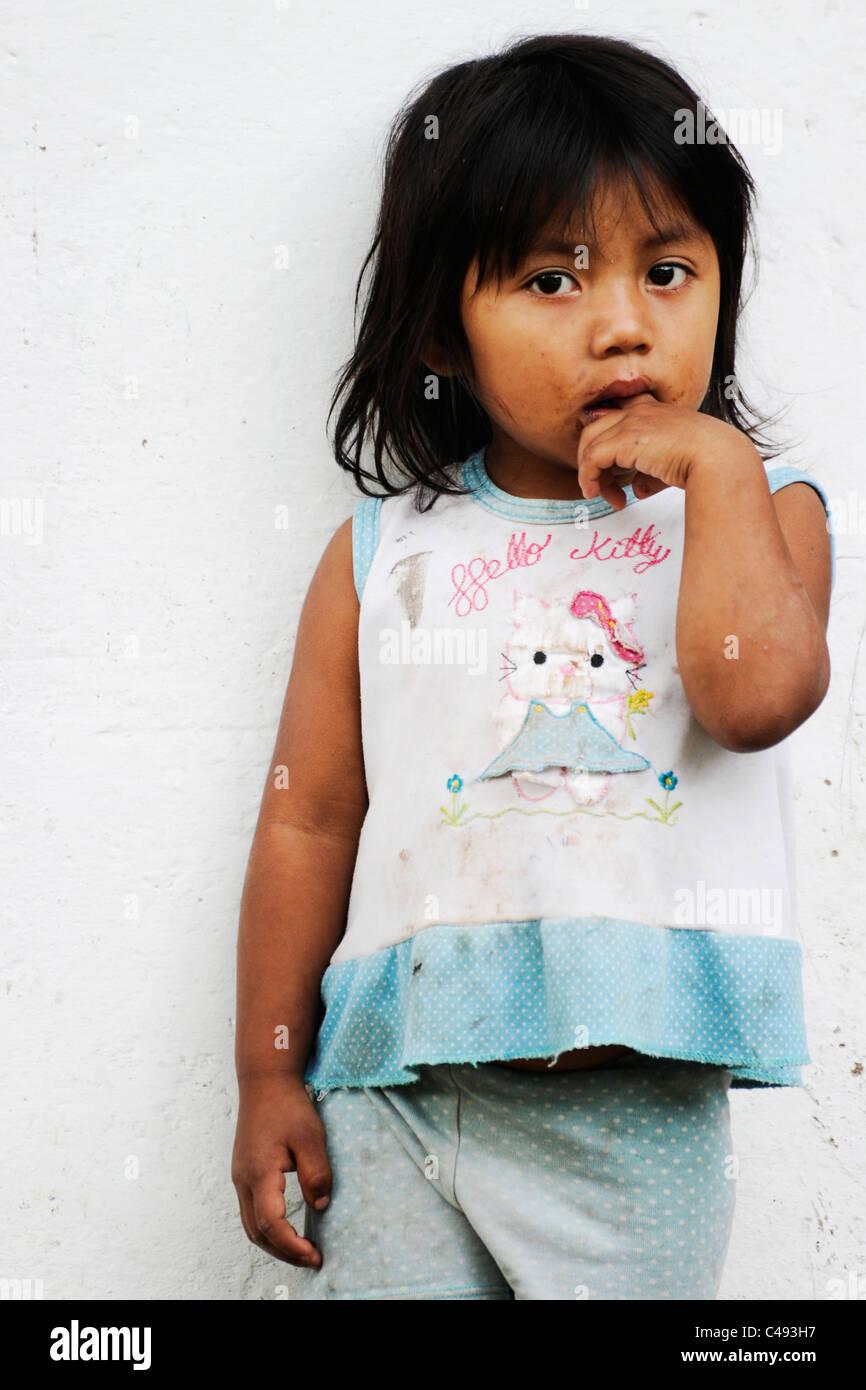 Un bambino locale sta solo contro la parete della sua casa, Tierra dentro, Colombia meridionale Immagini Stock
