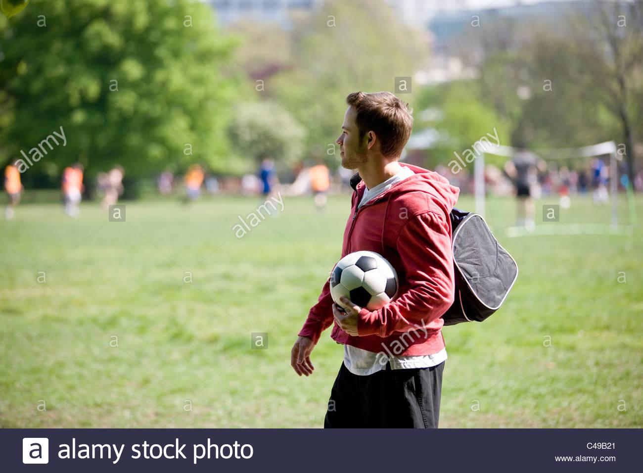 Un giovane uomo in piedi nel parco, portante un calcio e una borsa sportiva Immagini Stock