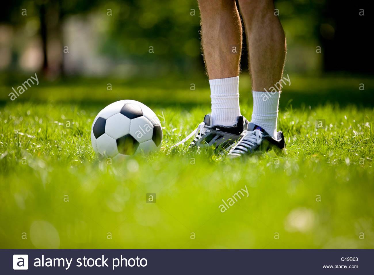 Un giovane uomo in piedi accanto a un campo di calcio, close-up Immagini Stock