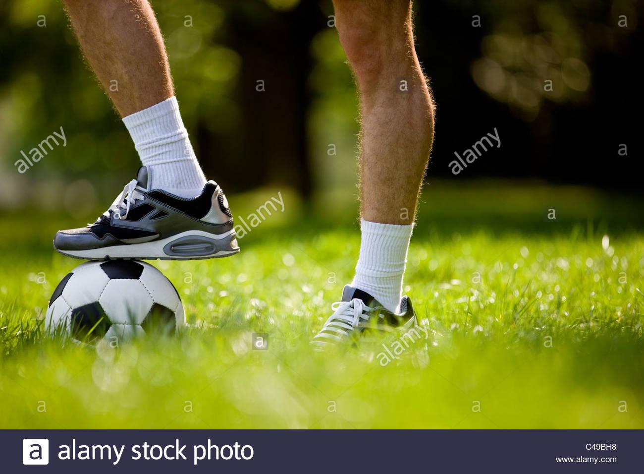 Un giovane uomo con il suo piede su un campo di calcio, close-up Immagini Stock