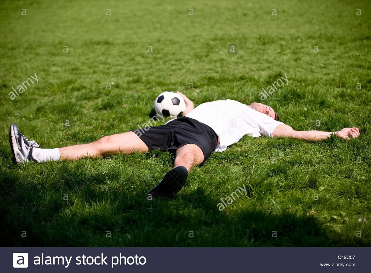 Un giovane uomo disteso sull'erba, tenendo in mano un pallone da calcio Immagini Stock