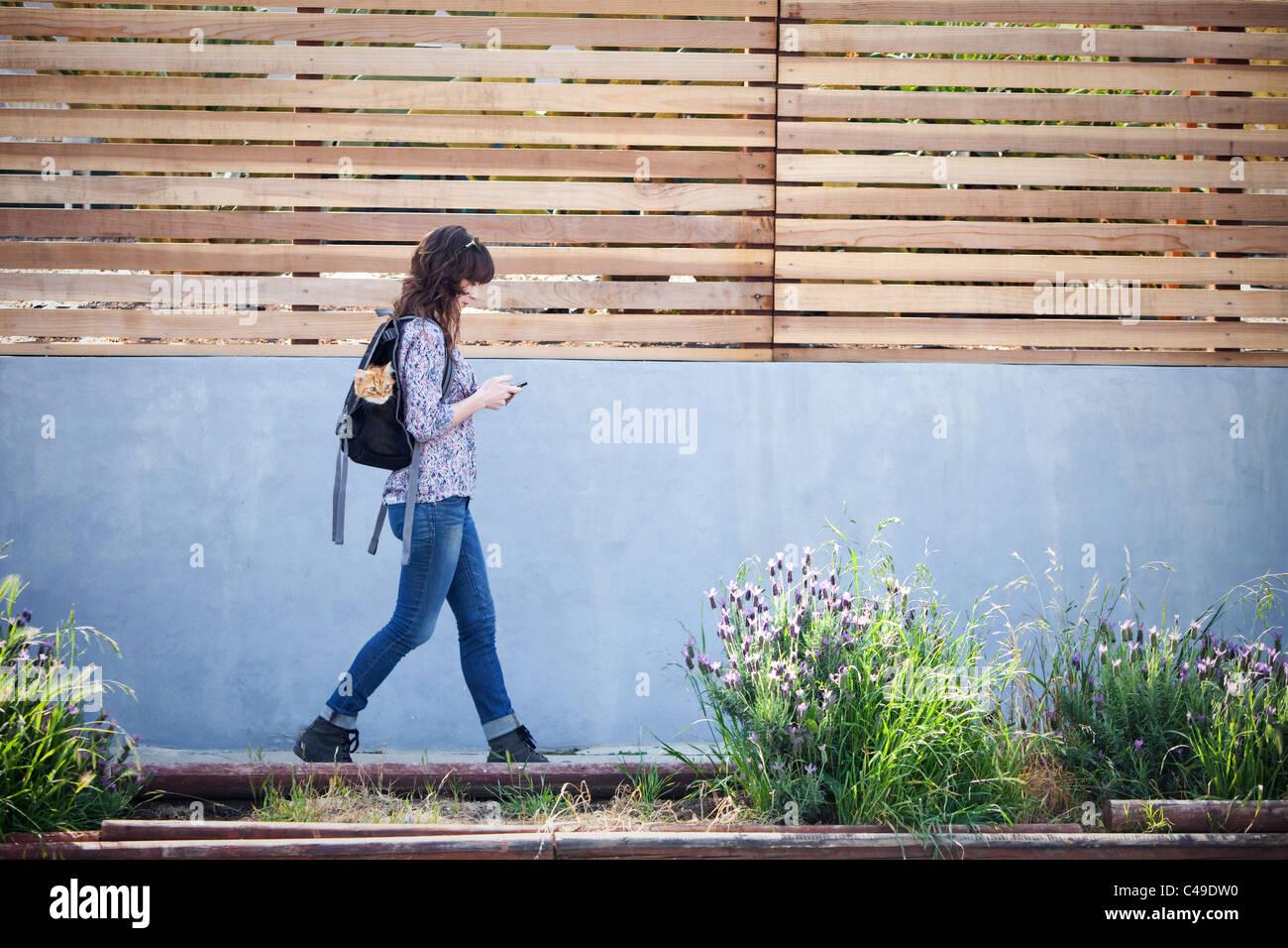 Una donna che cammina verso il basso quartiere urbano marciapiede con un gatto nel suo zaino. Immagini Stock