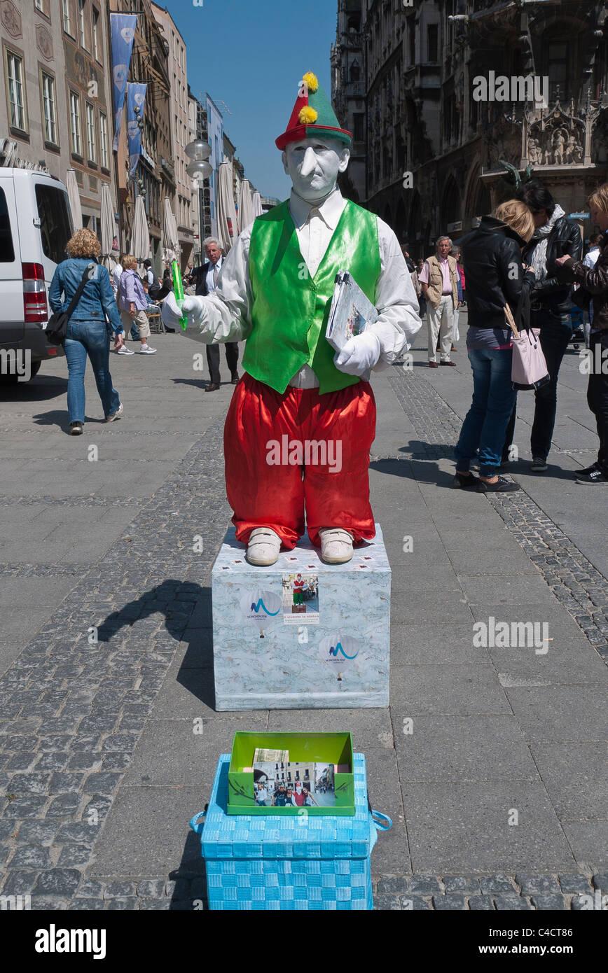 Un esecutore di strada vestiti in abiti da clown con un dipinto di bianco di  viso e lunga tipo Pinocchio naso esegue a Monaco di Baviera 714eb428d28