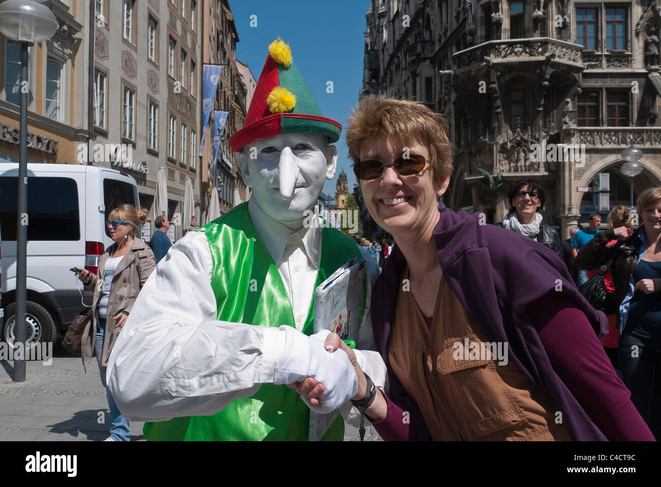 Un esecutore di strada vestiti in abiti da clown con un dipinto di bianco di  viso e lunga tipo Pinocchio naso detiene una donna di mano. b92f03b398e