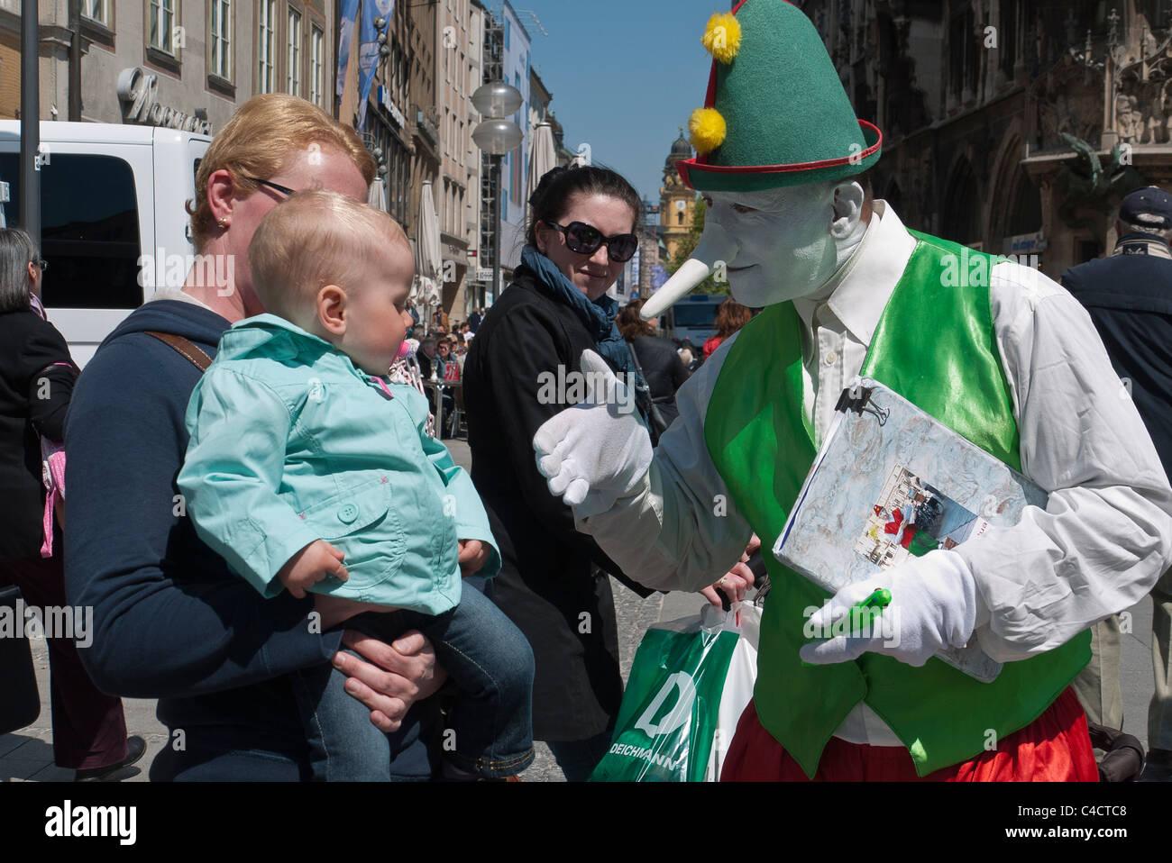 Un esecutore di strada vestiti in abiti da clown con un dipinto di bianco di  viso e lunga tipo Pinocchio naso tiene per mano un bambino. c8af5d30cf3