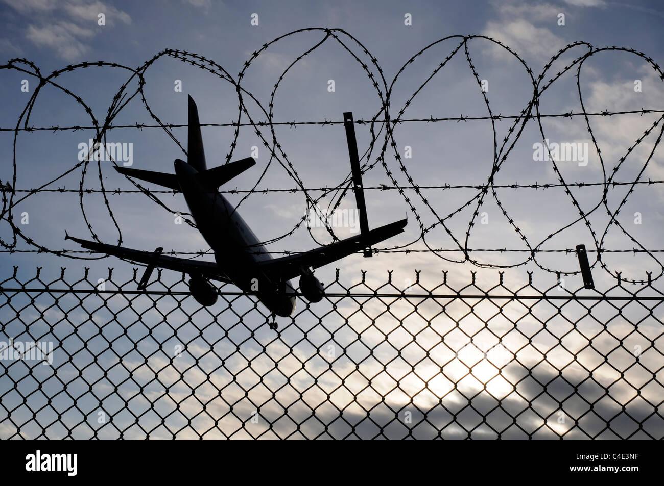 Un piano di sbarco che attraversa il filo spinato recinzioni perimetrali all'Aeroporto di Londra Heathrow Immagini Stock