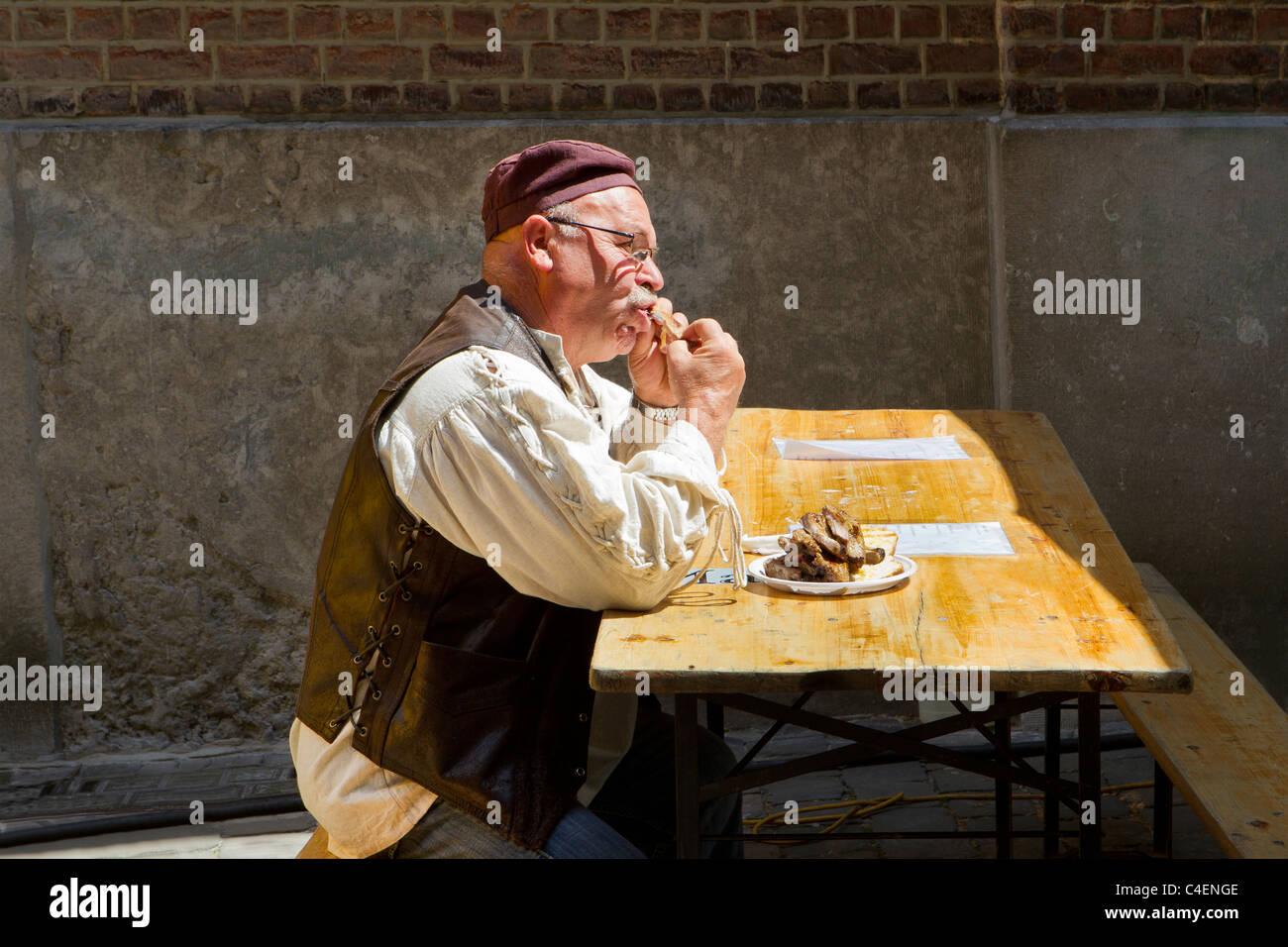 Uomo in costume tradizionale di mangiare costolette di maiale Immagini Stock