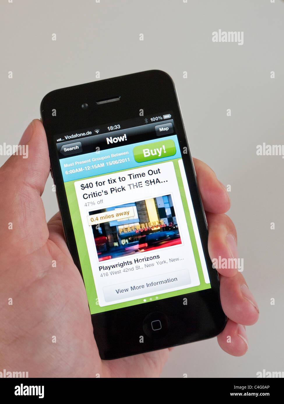 Utilizzando Groupon app per la ricerca di trattativa in New York City su iPhone 4G smart phone Immagini Stock