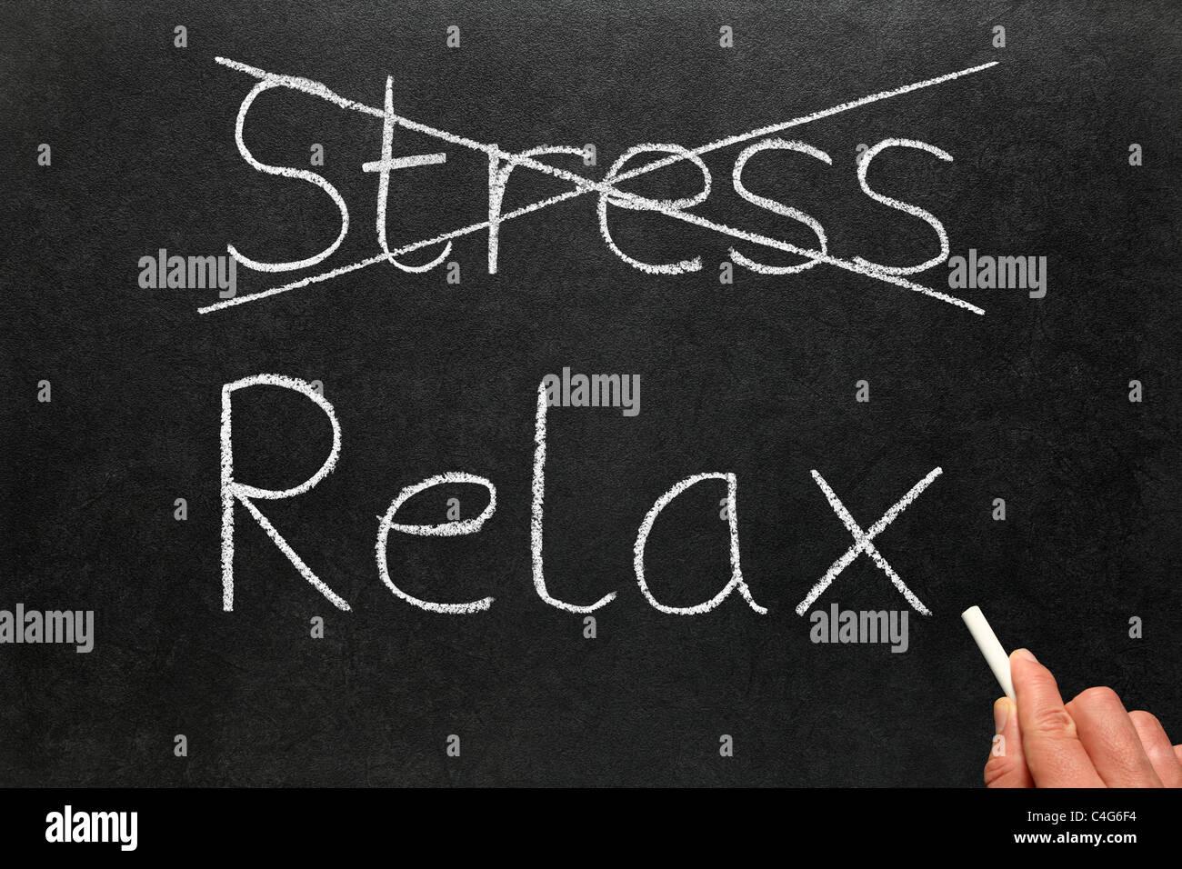 Attraversamento fuori lo stress e la scrittura di rilassarsi con il bianco gesso su una lavagna. Immagini Stock