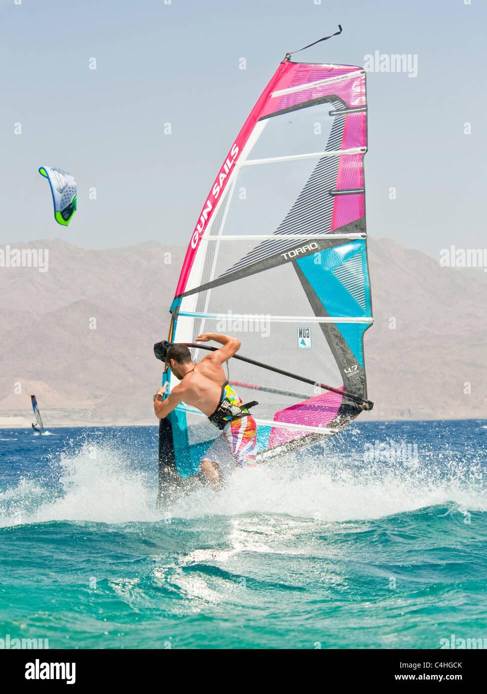 Un windsurf eseguendo acrobazie sul mar rosso presso il resort di Eilat in Israele. Foto Stock