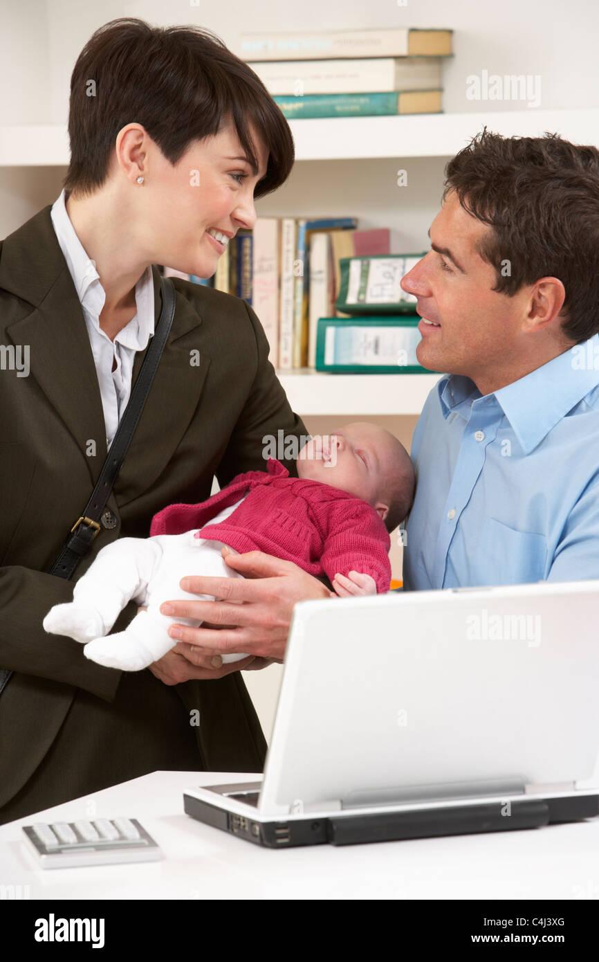 Madre di lavoro lasciando il bambino con il padre che lavora da casa Foto Stock