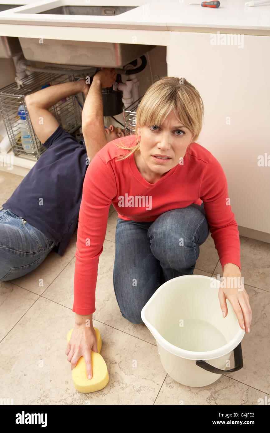 La donna dovrà asciugare perde lavandino mentre idraulico funziona Immagini Stock
