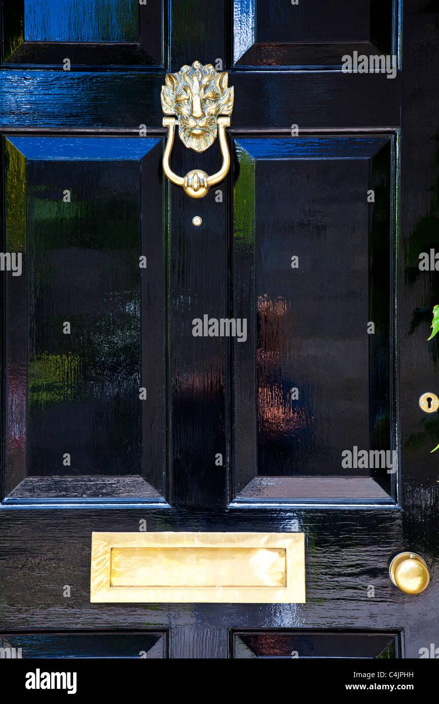 Un brillante High Gloss Black dipinta porta anteriore con altamente lucidato porta in ottone mobili. Immagini Stock
