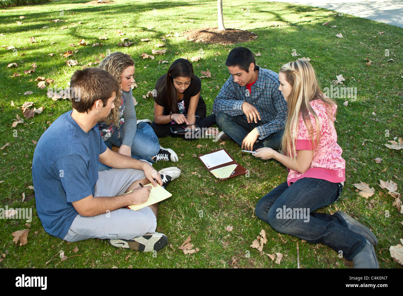Multi etnica minoranza razziale etnicamente diversi ragazzi di gruppo per studiare insieme utilizzando iphone cellulare Foto Stock
