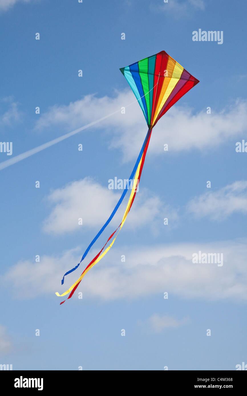 Rainbow kite battenti su una stringa con un blu cielo nuvoloso, Hampshire, Inghilterra, Regno Unito Foto Stock