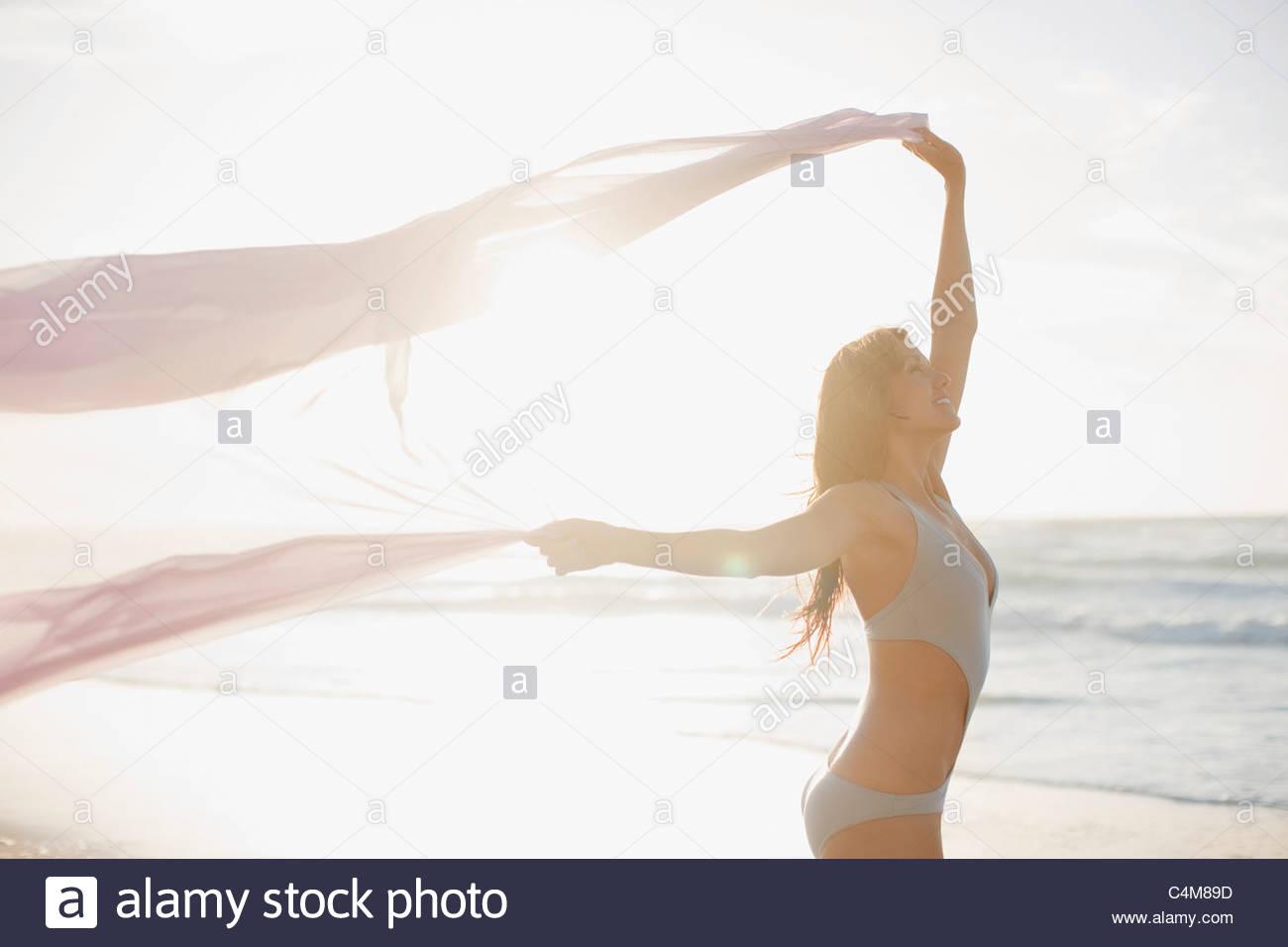 Donna che mantiene sarong overhead sulla spiaggia Immagini Stock