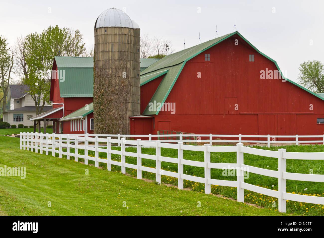 Un caseificio rosso fienile con recinto bianco in Middlebury, Indiana, Stati Uniti d'America. Immagini Stock