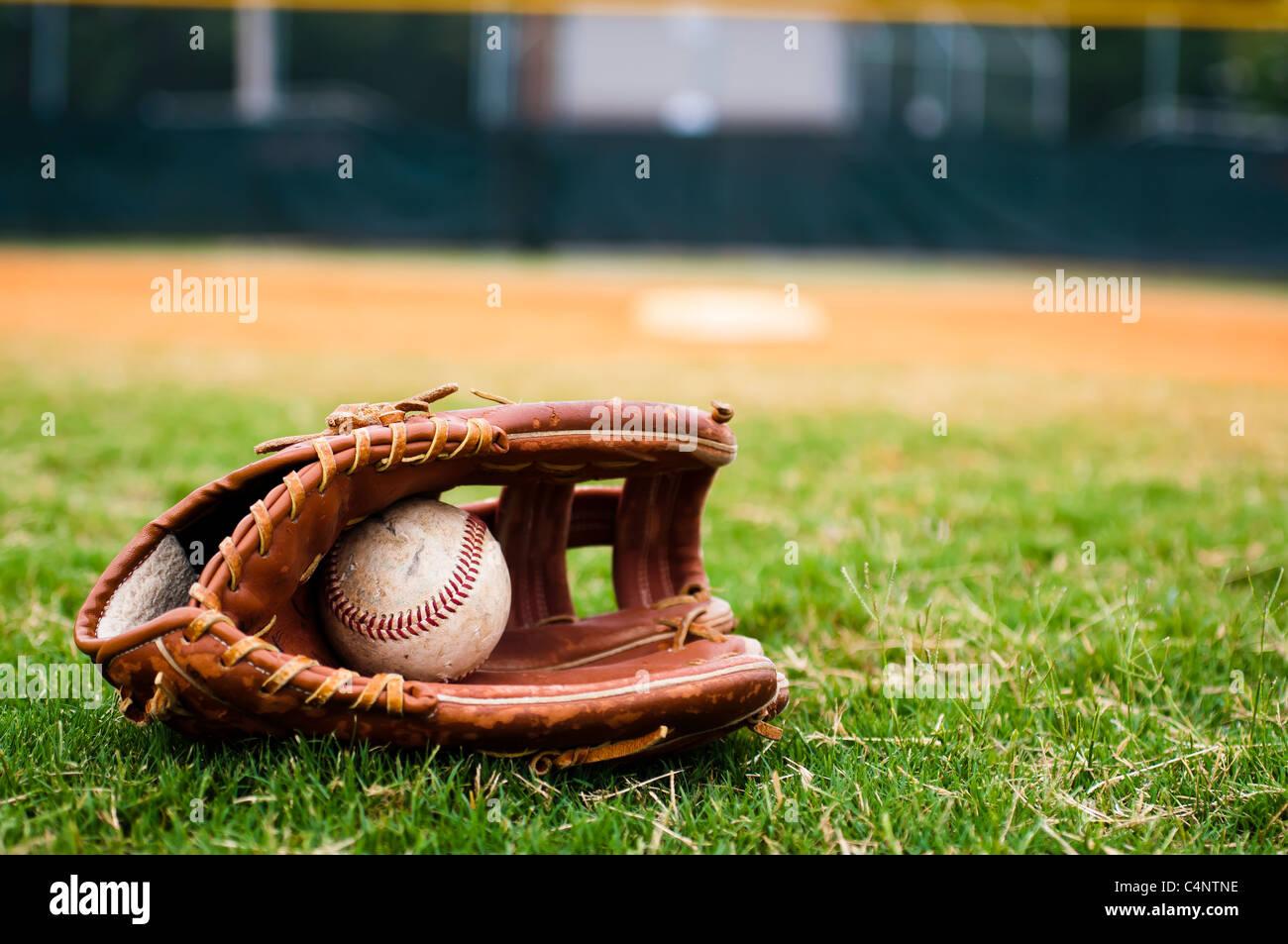 Il baseball in guanto sul campo con base fuori campo lato e in background. Immagini Stock