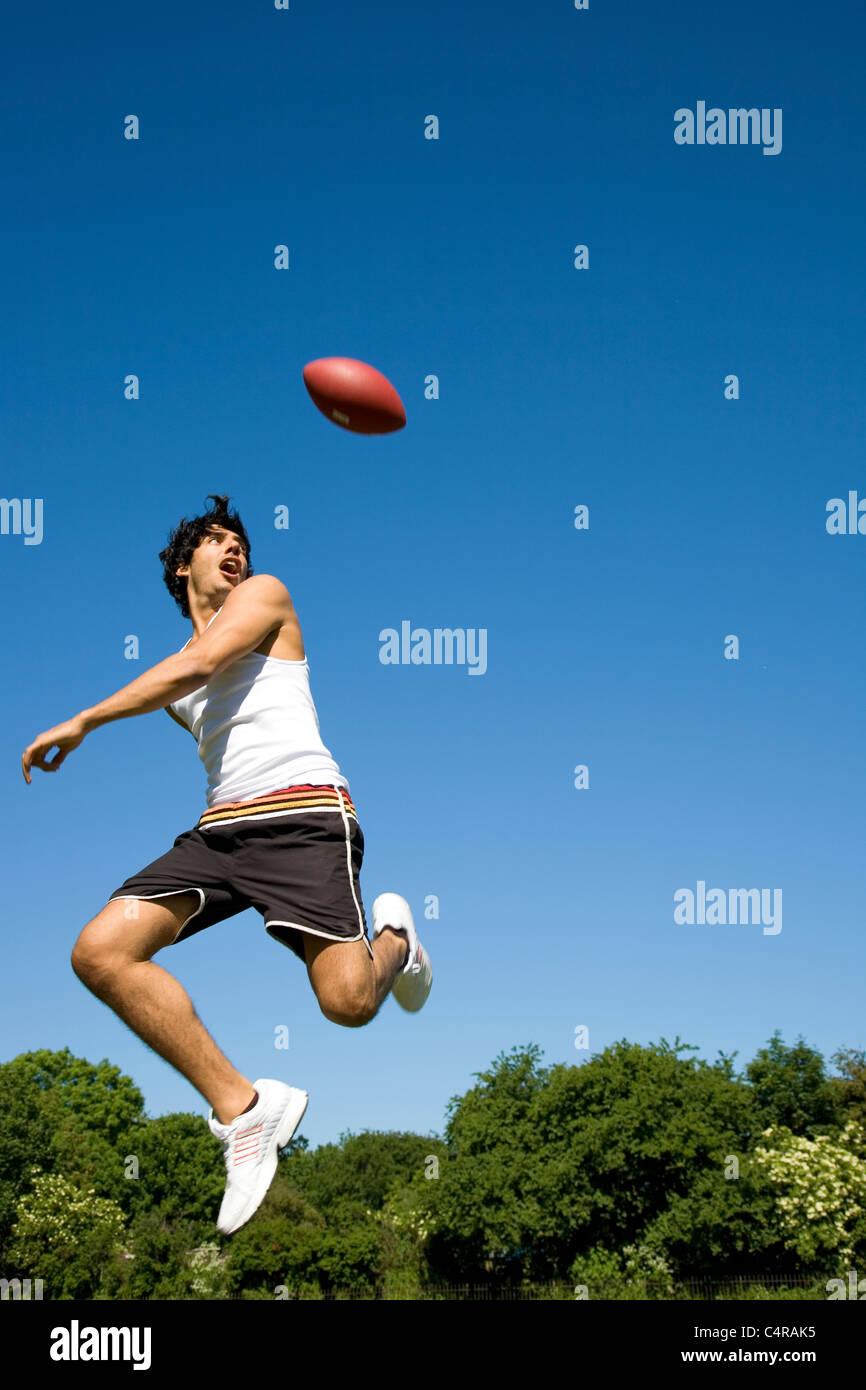 L'uomo jumping gioca con la palla ovale in posizione di parcheggio Immagini Stock