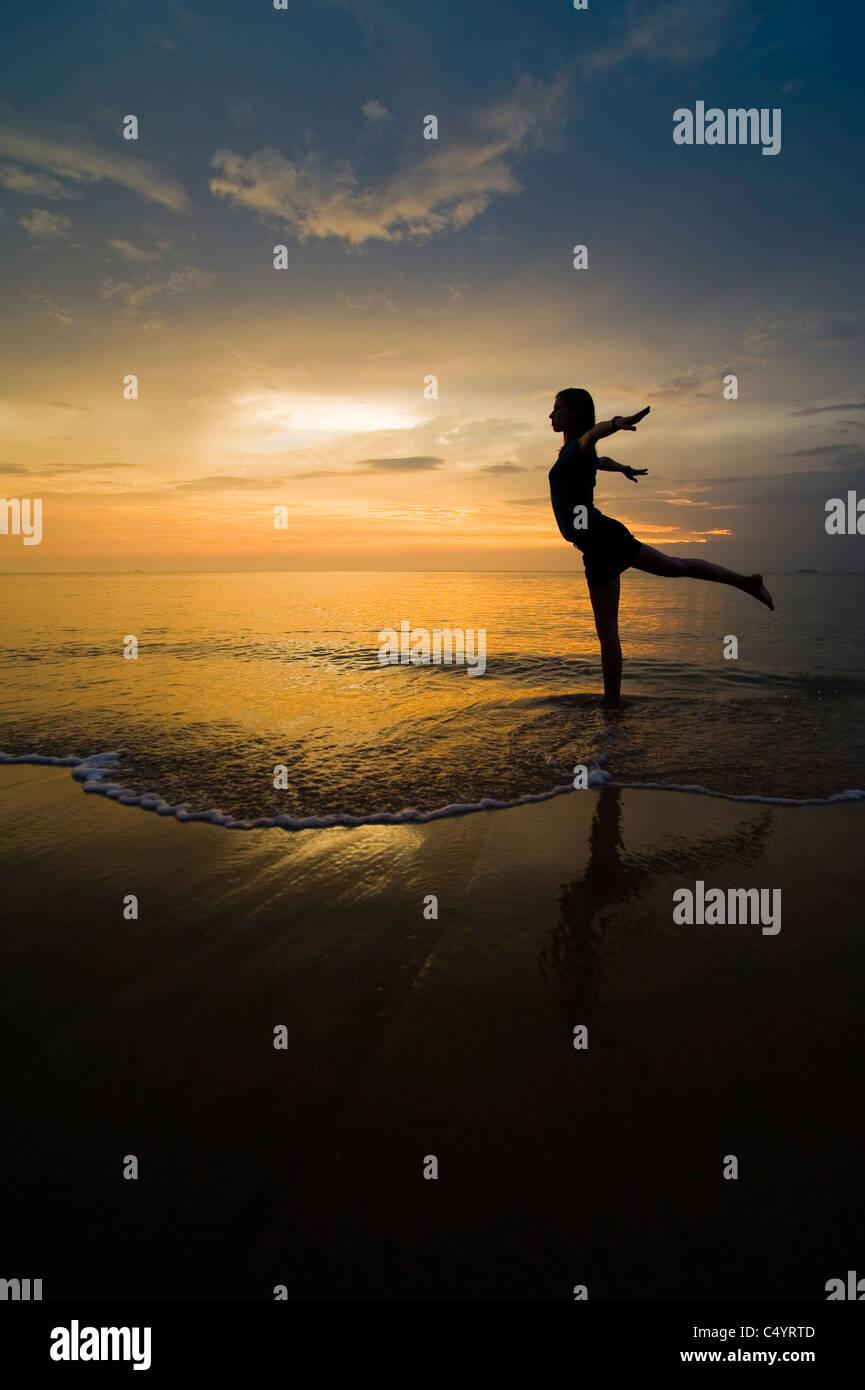 Una giovane donna facendo esercizi yoga sulla spiaggia al tramonto.Preso in Phra Ae Beach (Long Beach), Koh Lanta Immagini Stock