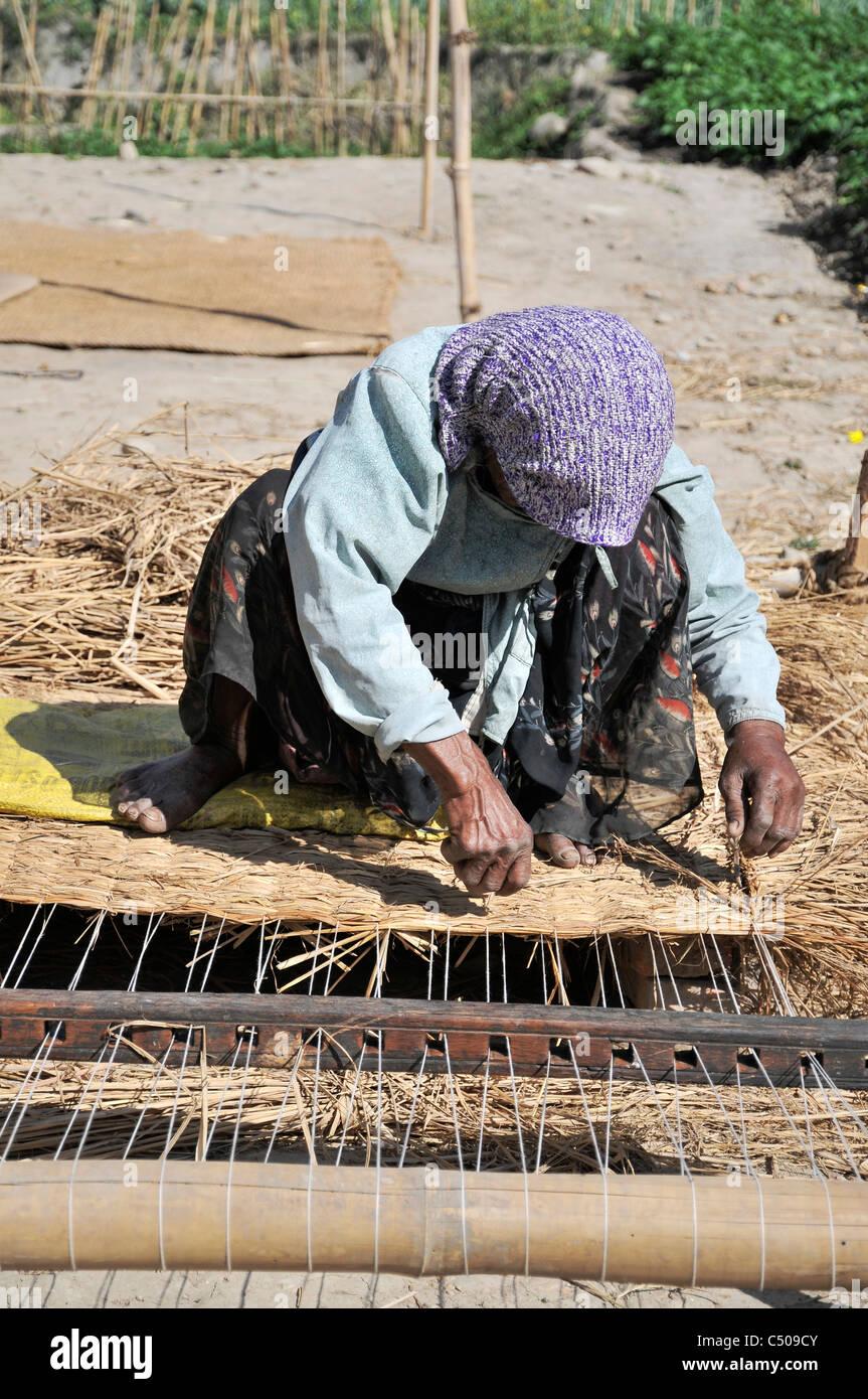 Il nepalese donna tessitura di un materasso in Baktapur. Immagini Stock