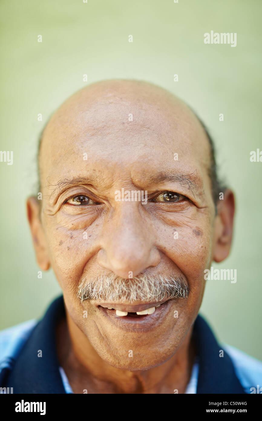 Ritratto di senior uomo ispanico con problemi dentali guardando la telecamera contro la parete verde. Forma verticale Immagini Stock