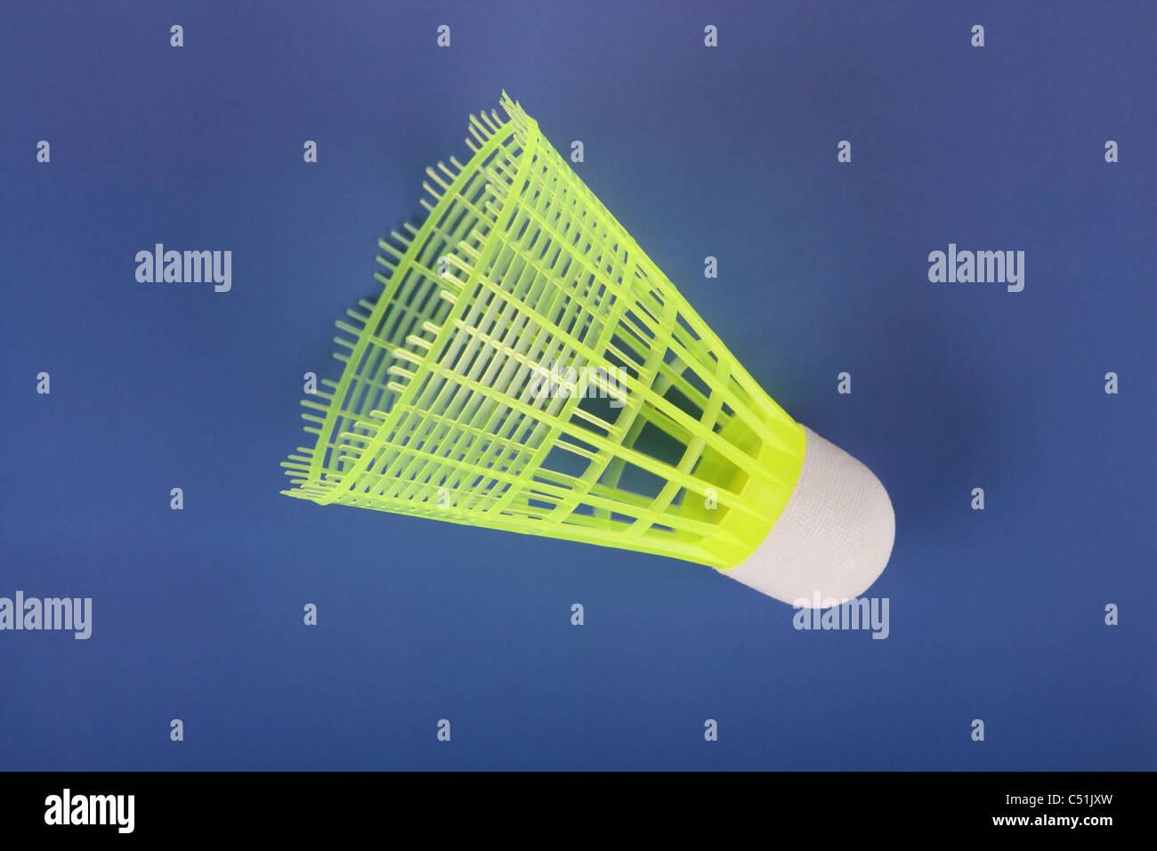 Uno giallo badminton volano su uno sfondo blu scuro Immagini Stock