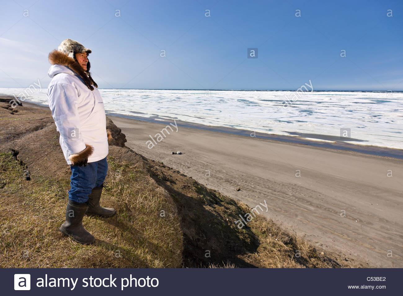 Inupiaq eschimese hunter permanente al vecchio Utkeagvik originale sito cittadina che si affaccia sul mare Chukchi, Immagini Stock