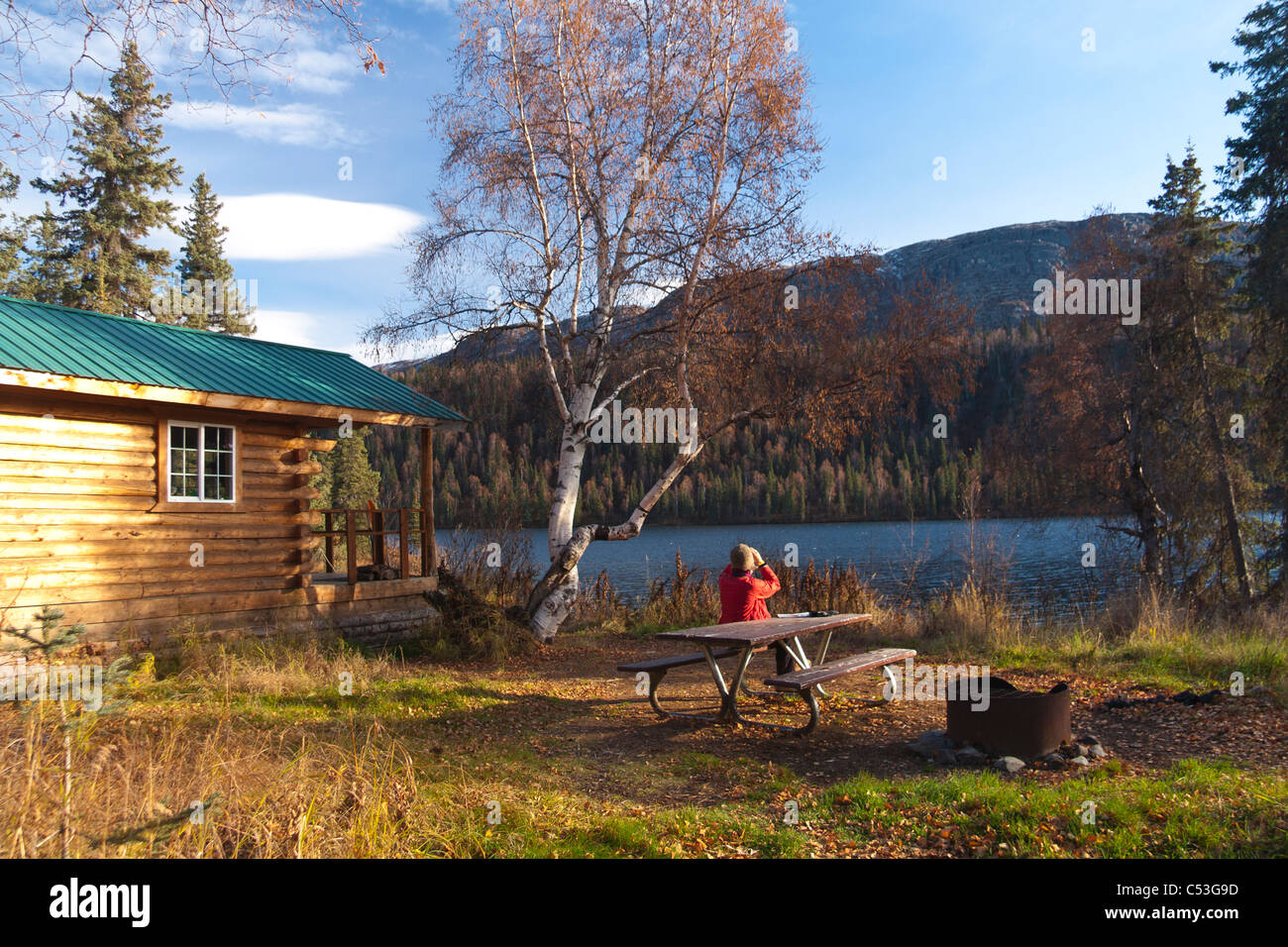 La donna gode guardando le viste attraverso il binocolo mentre a un tavolo da picnic, Byers Lago di uso pubblico Immagini Stock