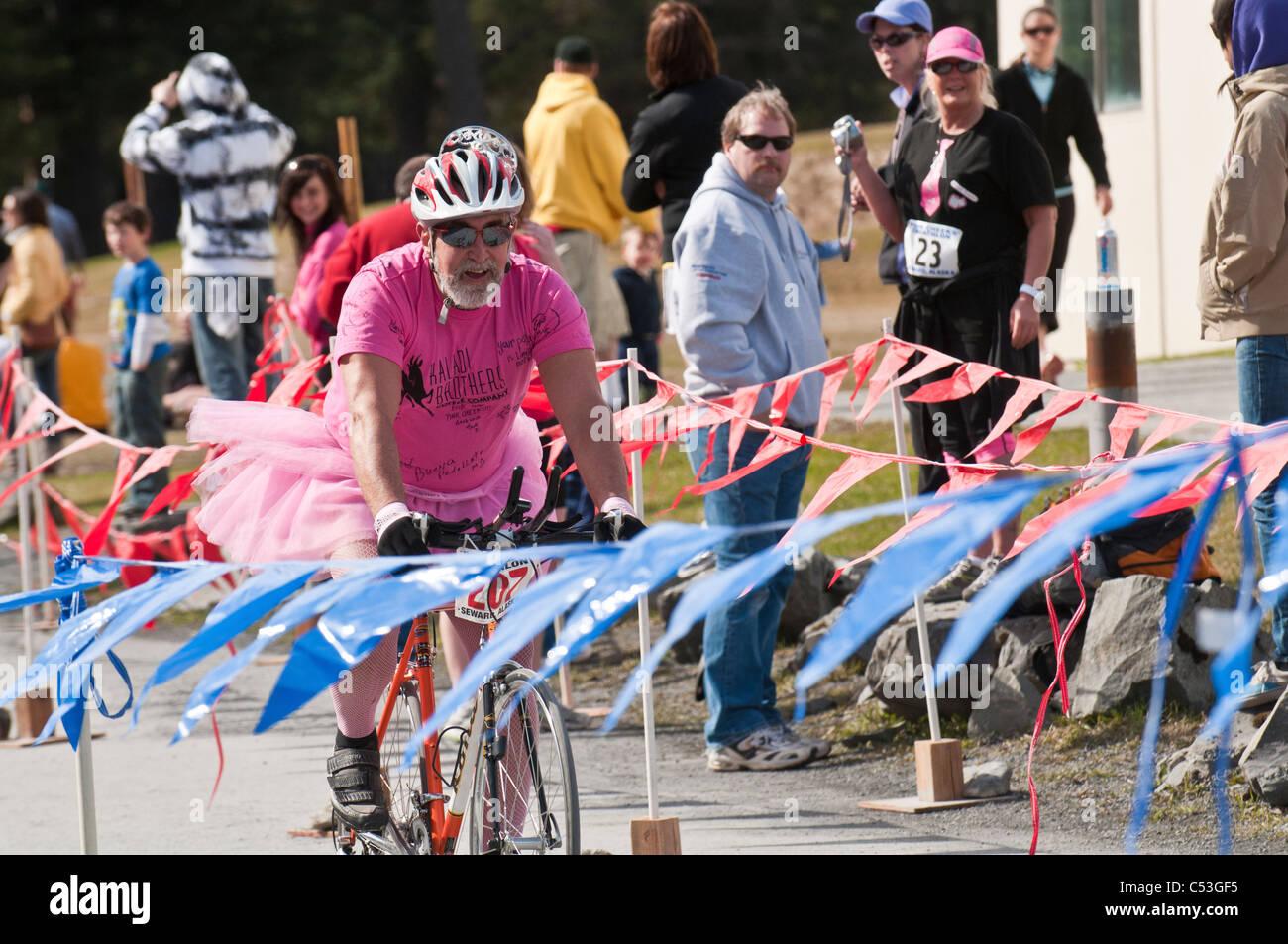 L'uomo vestito di una maglia rosa e costume tutu bici sulla linea del traguardo durante le guance Rosa Triathlon, Seward, Alaska Foto Stock
