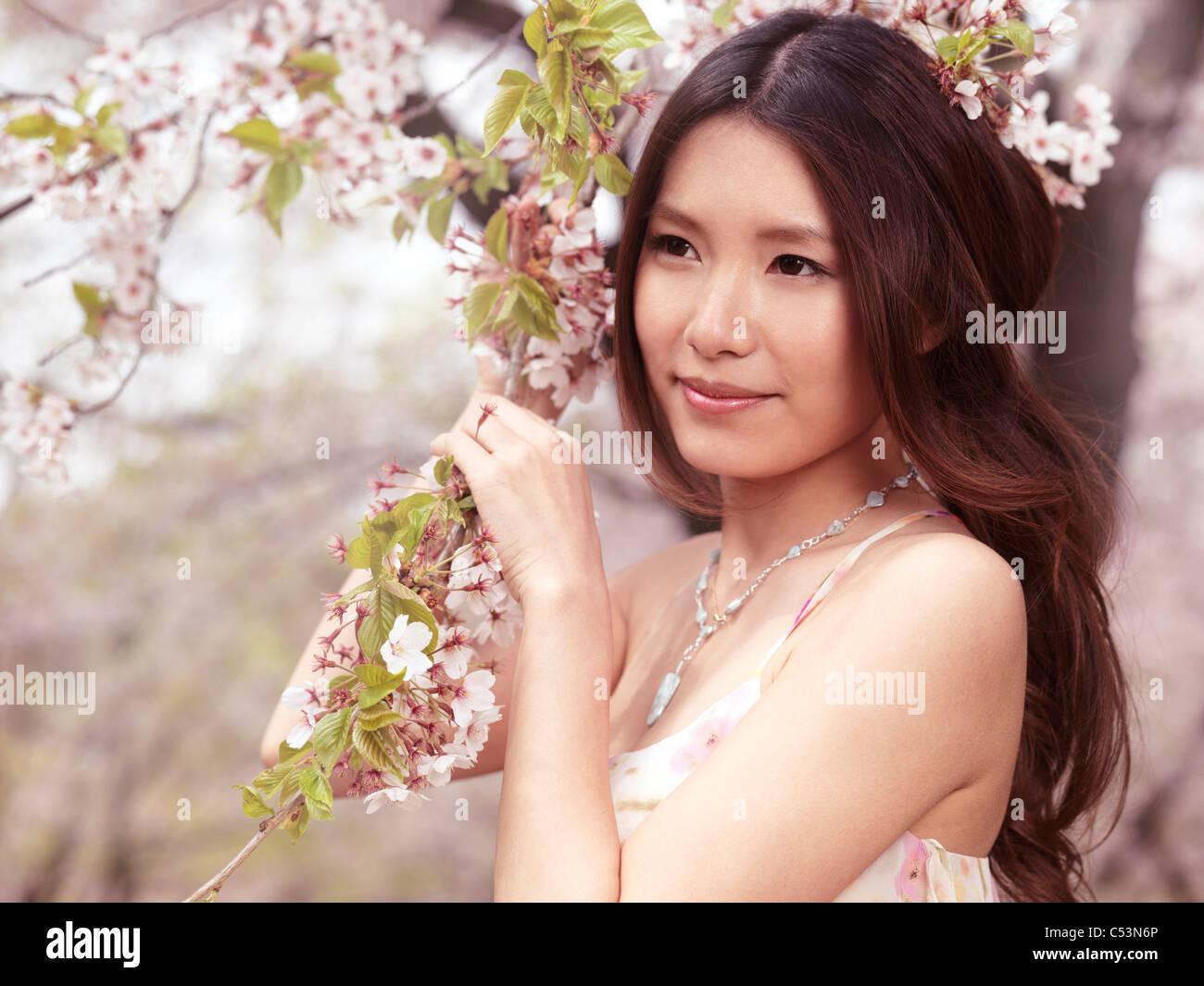 Ritratto di una giovane e bella sorridente donna asiatica sta in piedi in una fioritura di ciliegio in un parco Immagini Stock