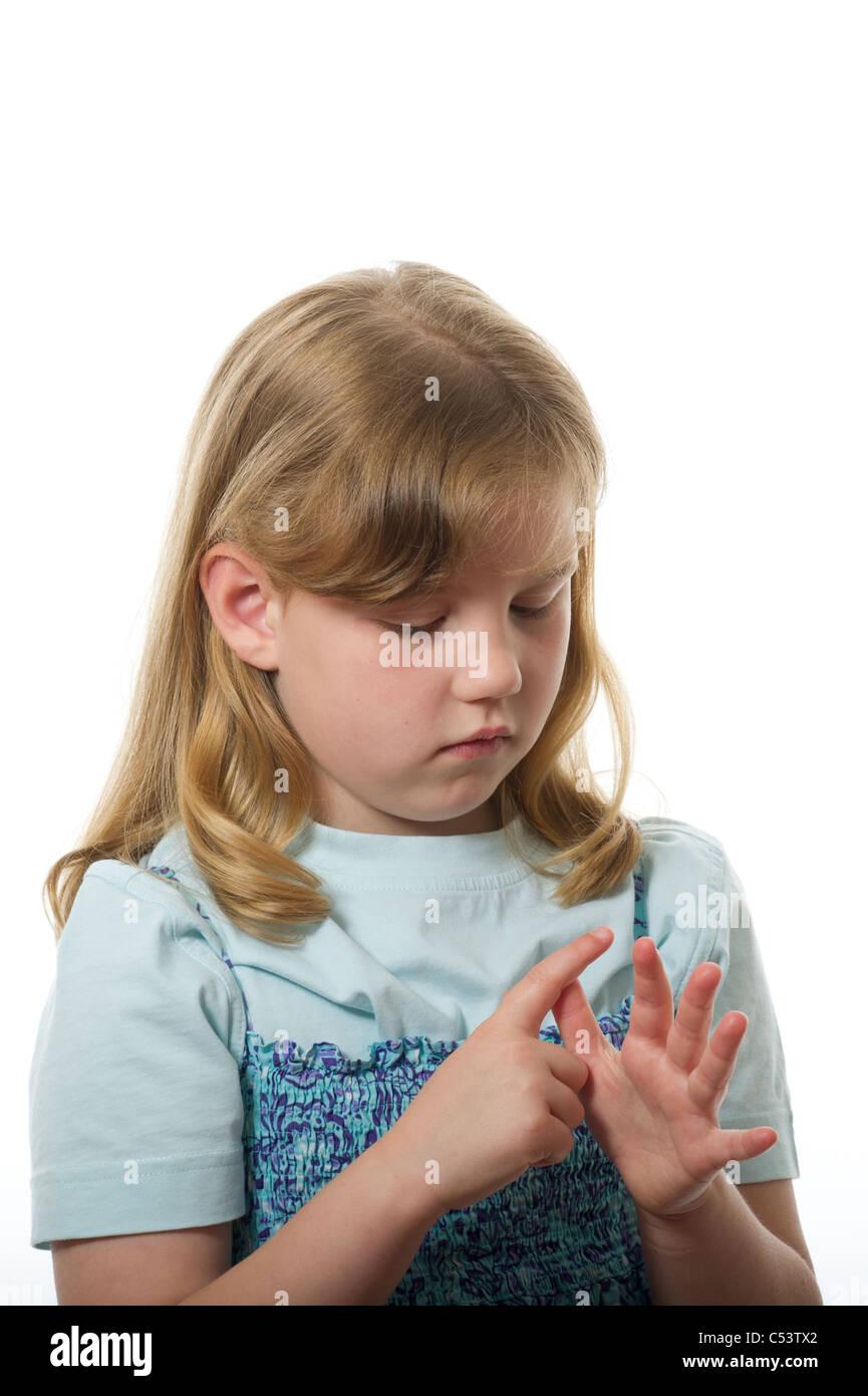 Un giovane età primaria ragazza facendo inoltre contando sulle sue dita fotografati contro un bianco di sfondo Immagini Stock