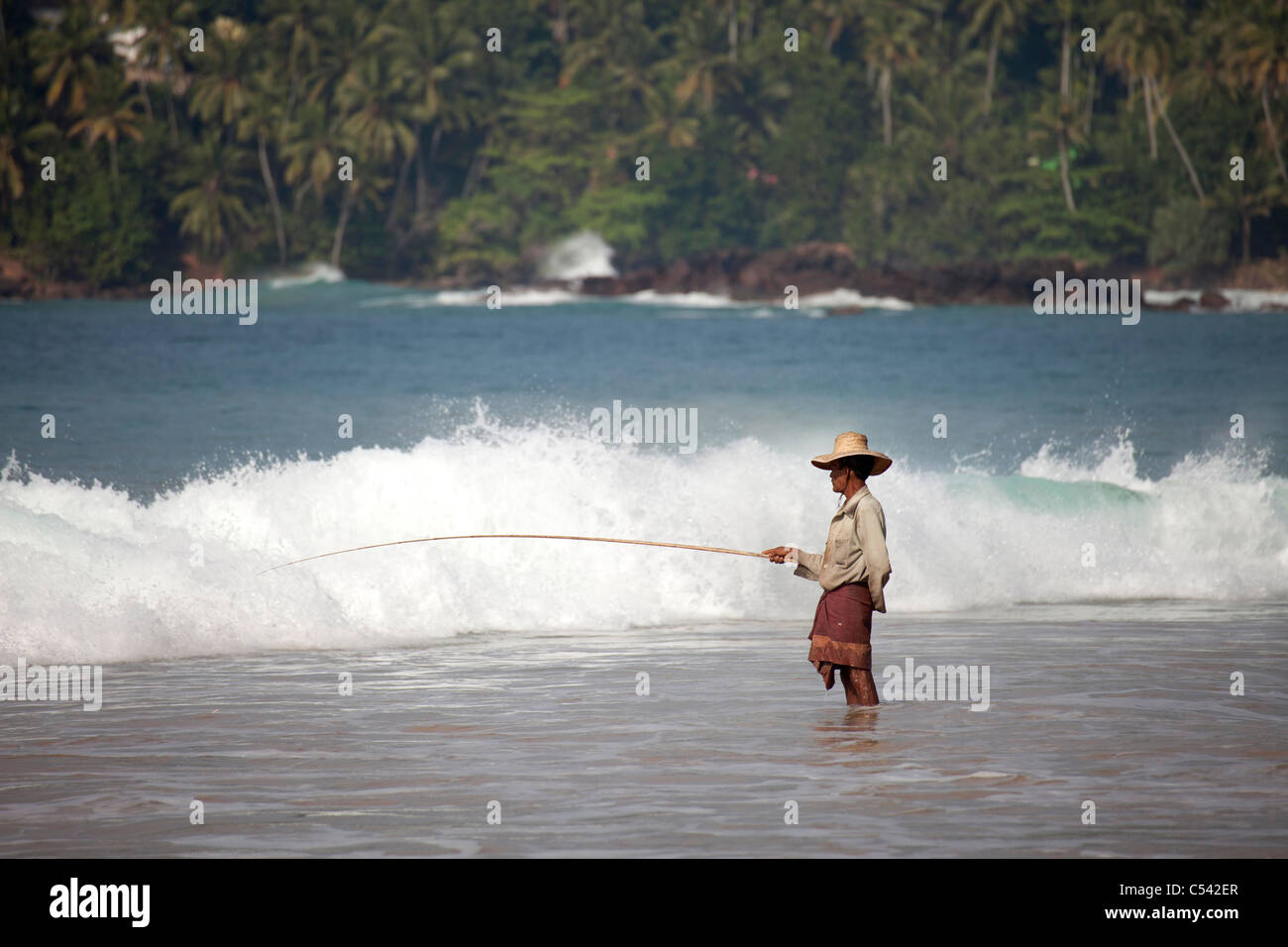 Fisherman angling in onde di Mirissa beach, Sri Lanka Immagini Stock
