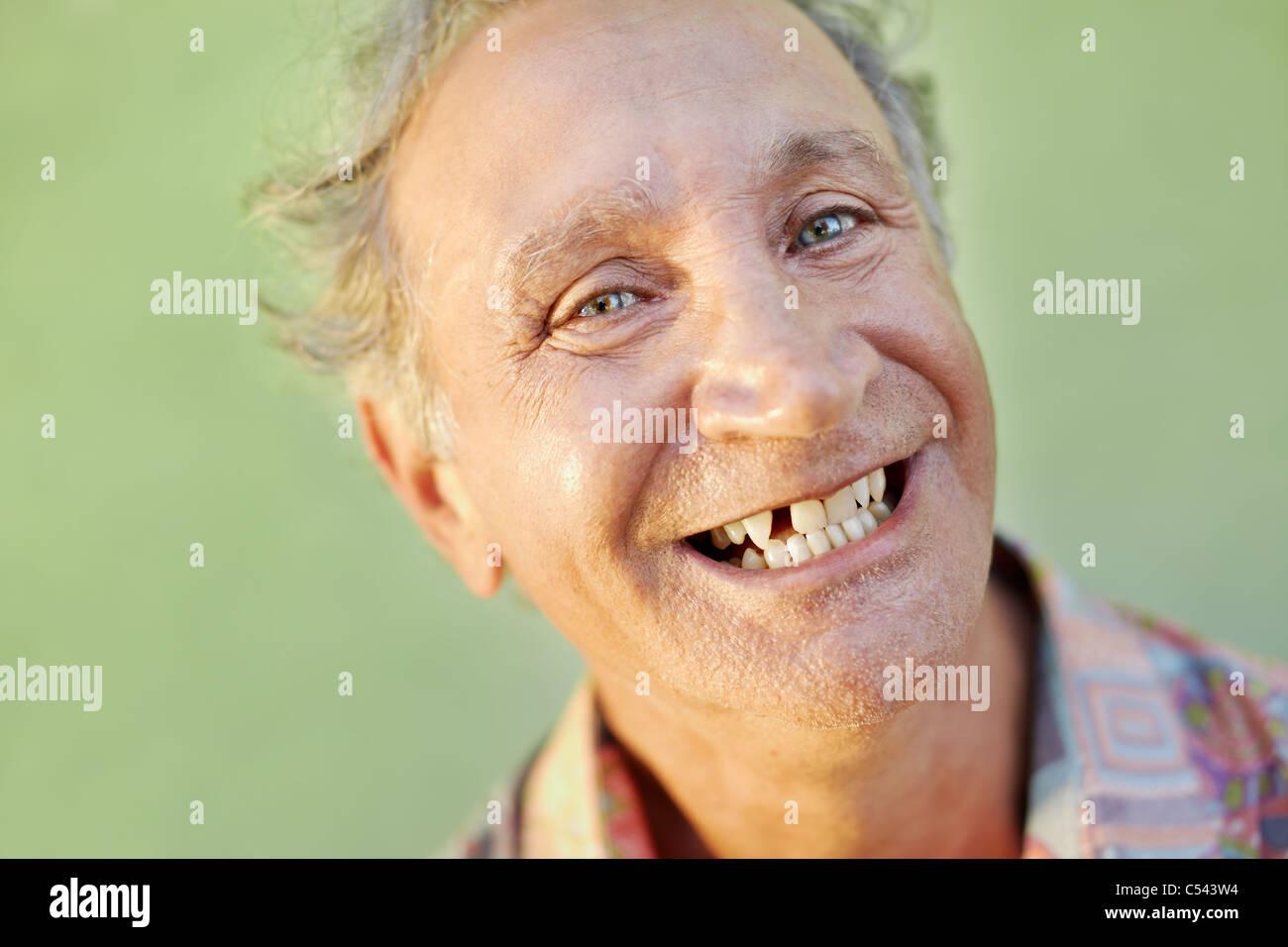 Ritratto di senior uomo caucasico con problemi dentali che mostra dente mancante e sorridente. Sagoma orizzontale, Immagini Stock