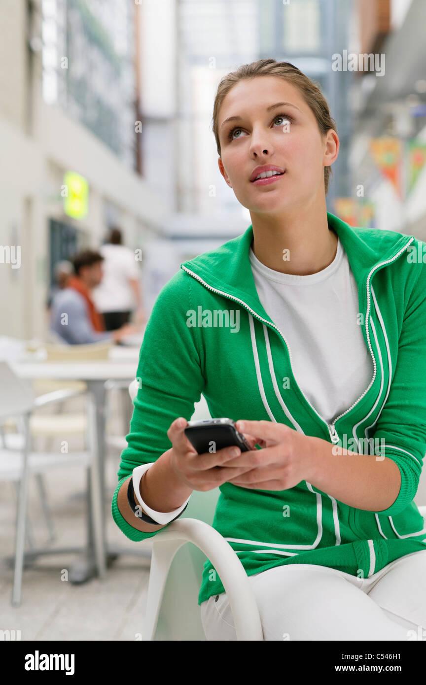 Bella donna utilizzando il telefono cellulare nella lobby di università Foto Stock