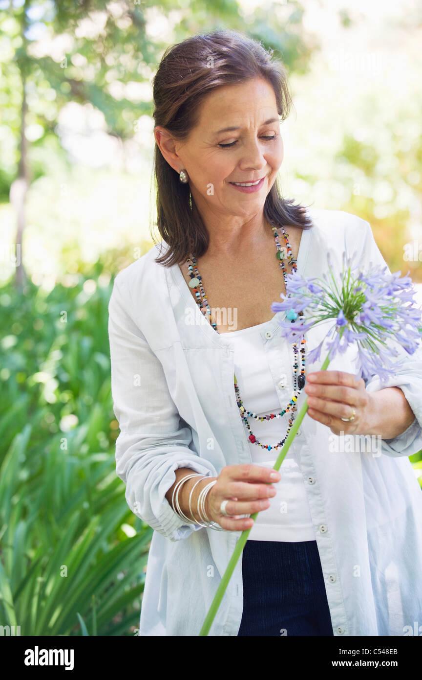Donna sorridente tenendo un unico fiore in mano Immagini Stock