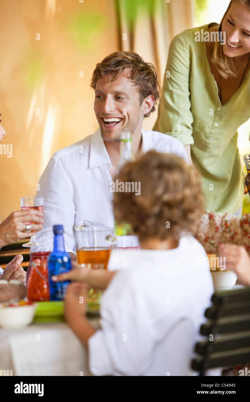 Famiglia avente le bevande e discute al tavolo da pranzo Foto Stock
